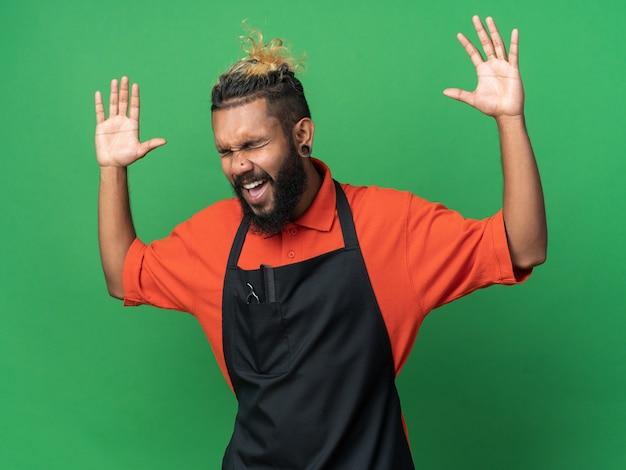 Gestresste jonge afro-amerikaanse mannelijke kapper die uniforme handen draagt die schreeuwen met gesloten ogen