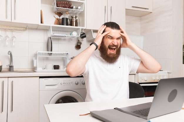 Gestresste jonge, bebaarde man heeft hoofdpijn terwijl hij thuis op de laptop werkt.