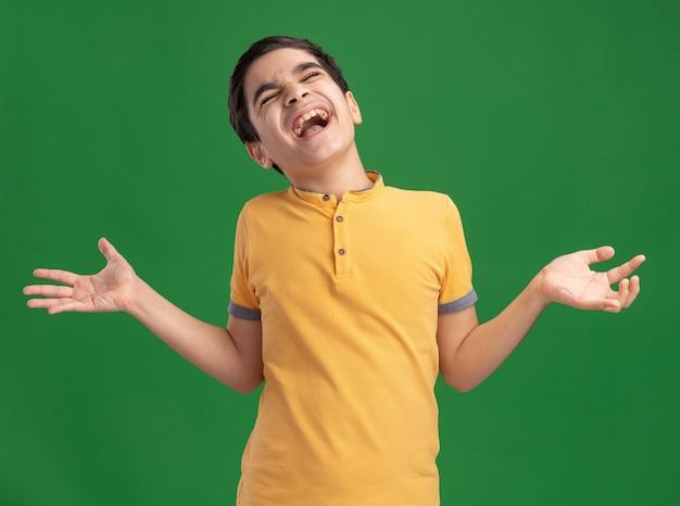 Gestresste jonge blanke jongen die lege handen laat zien die schreeuwen met gesloten ogen geïsoleerd op een groene muur