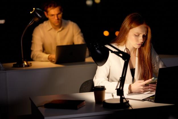 Gestresste jonge blanke vrouw die 's avonds laat op kantoor werkt en er slaperig uitziet, smartphone gebruikt, wat rust nodig heeft, overwerk overbelasting deadline werkconcept. ruimte kopiëren. focus op roodharige dame