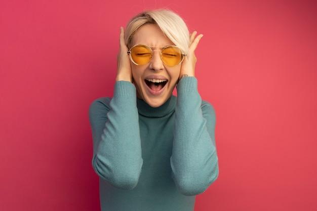 Gestresste jonge blonde vrouw die een zonnebril draagt die oren bedekt met handen die schreeuwen met gesloten ogen