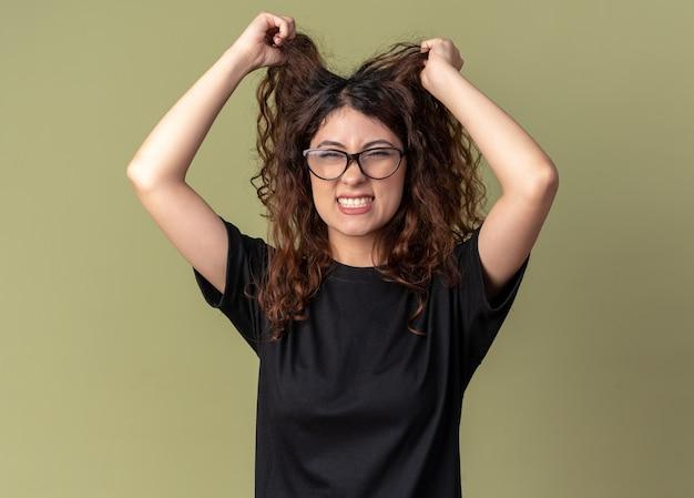 Gestresste jonge, mooie blanke vrouw met een bril die aan haar haar trekt
