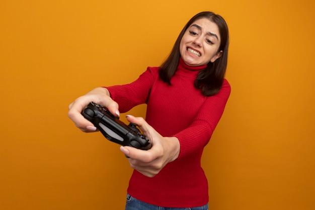 Gestresste jonge mooie vrouw die de joystick van de gamecontroller naar voren uitstrekt en ernaar kijkt terwijl ze een spel speelt geïsoleerd op een oranje muur met kopieerruimte