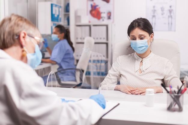 Gestresste jonge patiënt die masker draagt tegen coronavirus tijdens overleg met senior arts in het ziekenhuiskantoor.
