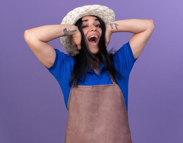 Gestresste jonge tuinmanvrouw die uniform en hoed draagt en naar de voorkant kijkt die oren bedekt die schreeuwen op een paarse muur