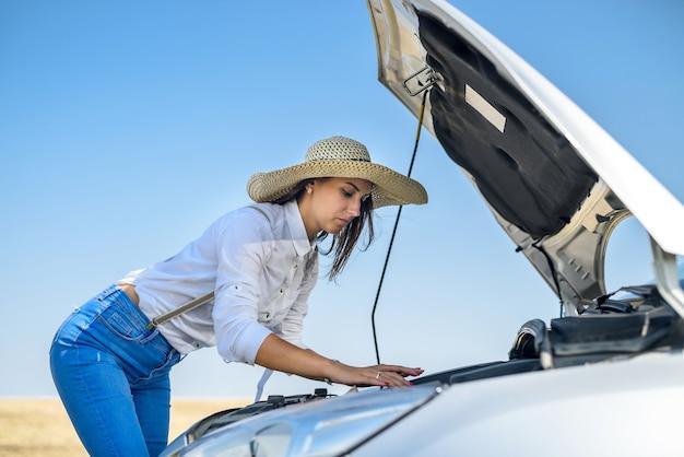 Gestresste jonge vrouw die naar de motor van haar auto kijkt. roadtrip problemen. de auto heeft een reparatie nodig.