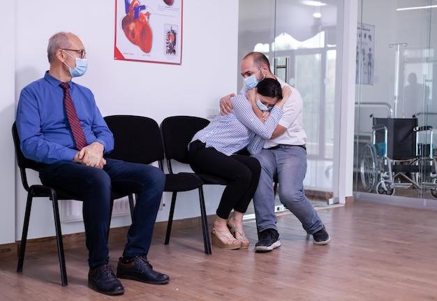 Gestresste jonge vrouw en echtgenoot met gezichtsmaskers die slecht nieuws ontvangen van de dokter in de wachtruimte van het ziekenhuis
