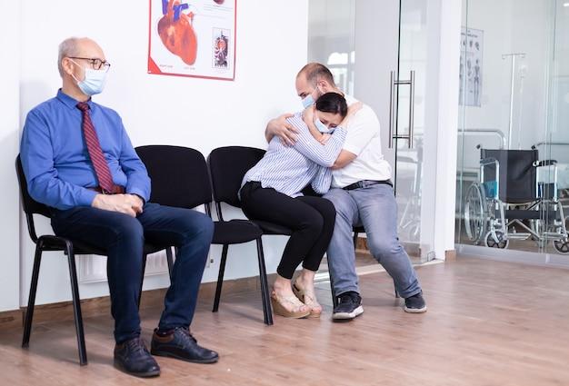 Gestresste jonge vrouw en echtgenoot na slecht nieuws van dokter in wachtruimte van ziekenhuis