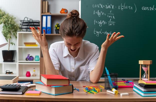 Gestresste jonge vrouwelijke wiskundeleraar die aan het bureau zit met schoolbenodigdheden die lege handen laten zien die schreeuwen met strak gesloten ogen in de klas