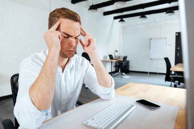 Gestresste jonge zakenman die zijn slapen aanraakt en hoofdpijn heeft op kantoor