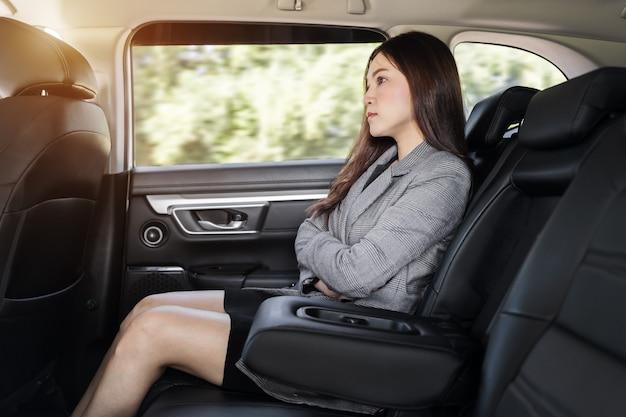 Gestresste jonge zakenvrouw die op de achterbank van de auto zit