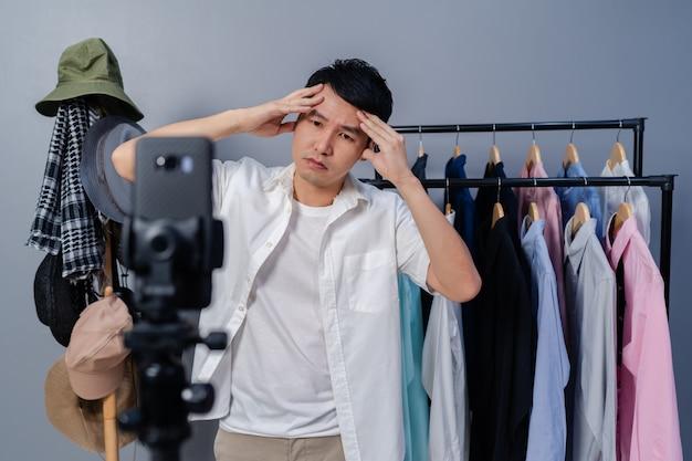 Gestresste jongeman kleding en accessoires online verkopen via smartphone live streaming, zakelijke online e-commerce thuis