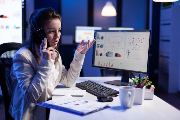Gestresste manager praat op smartphone met werknemer die aan financiële problemen werkt