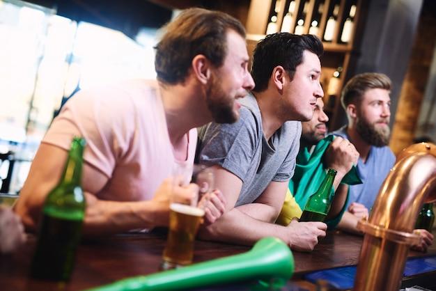 Gestresste mannen kijken geconcentreerd naar een wedstrijd