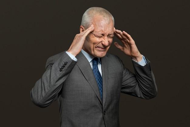 Gestresste senior zakenman die zijn hoofd aanraakt
