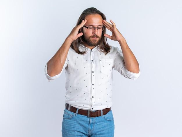 Gestresste volwassen knappe man met een bril die de handen op het hoofd houdt met gesloten ogen