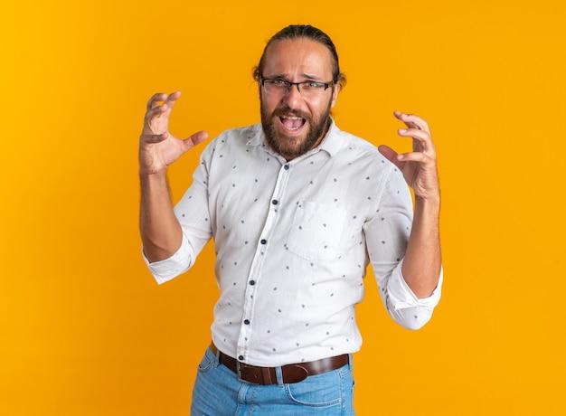 Gestresste volwassen knappe man met een bril die zijn handen in de lucht houdt schreeuwend Gratis Foto