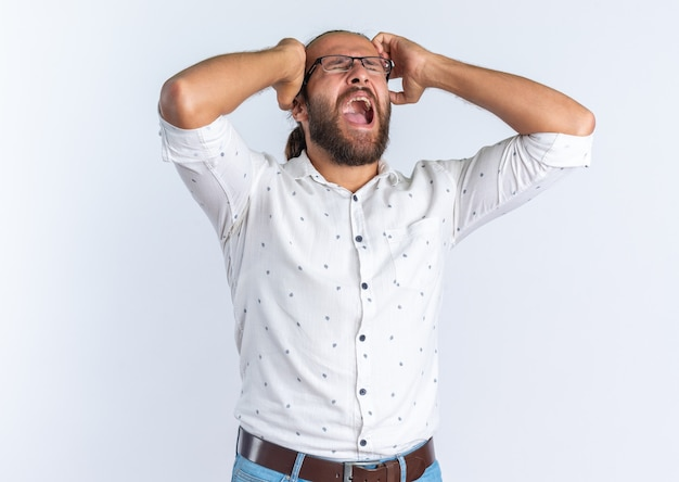 Gestresste volwassen knappe man met een bril die zijn handen op zijn hoofd houdt en schreeuwen met gesloten ogen geïsoleerd op een witte muur