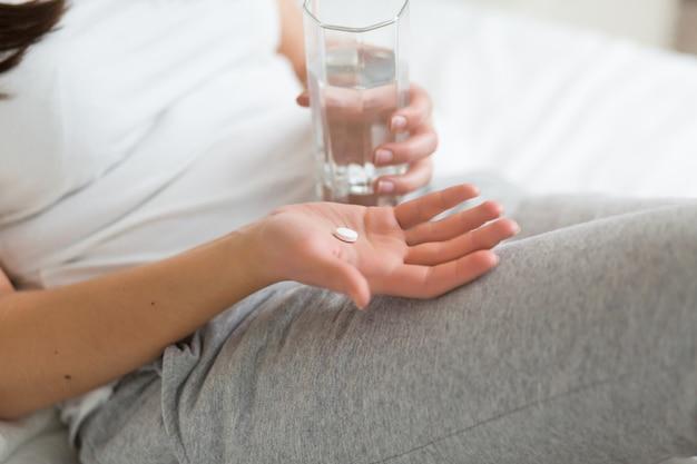 Gestresste vrouw die pil of medicijnen drinkt met glas water op bed thuis