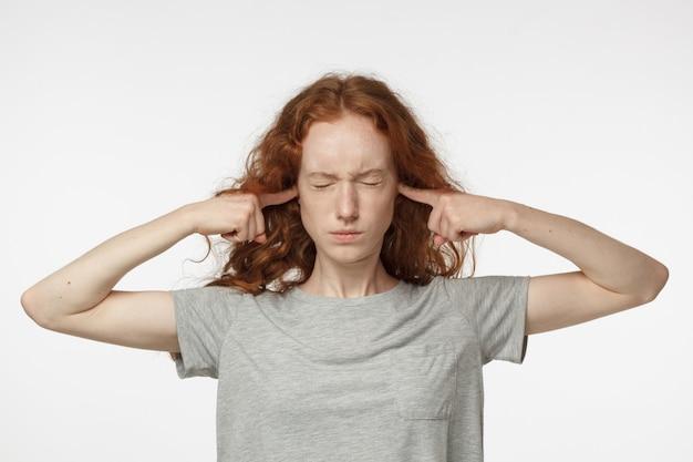 Gestresste vrouw stopt haar oren om het geluid van buren niet meer te horen
