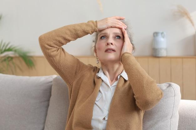 Gestresste vrouw van middelbare leeftijd zit op de bank in de woonkamer, in gedachten verzonken.
