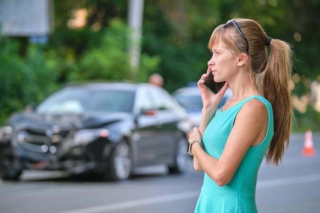 Gestresste vrouwelijke chauffeur die op de mobiele telefoon aan de straatkant praat en de hulpdiensten oproept na een auto-ongeluk. verkeersveiligheid en verzekeringsconcept.