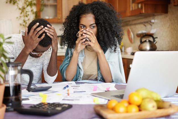 Gestresste werkloze echtgenoot met veel schulden die wanhopig het hoofd vasthoudt omdat hij geen rekeningen kan betalen