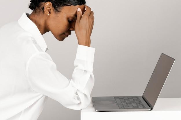 Gestresste zwarte vrouw die een laptop gebruikt