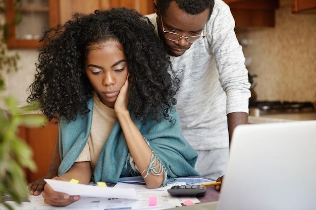 Gestrest afrikaans echtpaar met veel schulden die proberen hun huishoudelijke uitgaven te verminderen om geld te besparen