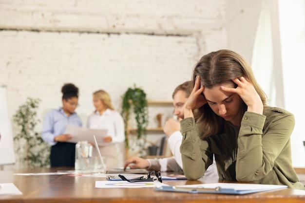 Gestrest. collega's werken samen in moderne kantoren met behulp van apparaten en gadgets tijdens creatieve vergadering.