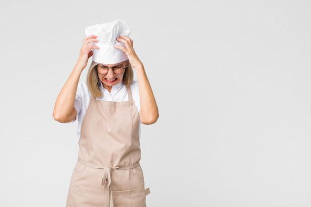 Gestrest en gefrustreerd voelen, de handen in de lucht steken, zich moe, ongelukkig voelen en met migraine