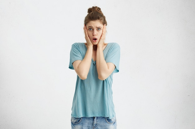 Gestrest geschokt jonge europese vrouw met handen op haar wangen en mond viel open verrast met onverwacht onaangenaam nieuws, kan haar oprechte emoties niet verbergen