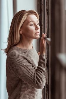 Gestrest voelen. blauwogige volwassen aangename vrouw die door het raam kijkt en zich gestrest voelt