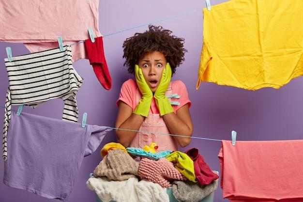 Gestreste, geschokte vrouw met afro-kapsel doet thuis de was, hangt nat schoon linnen aan de waslijn, draagt vrijetijdskleding en rubberen handschoenen, stomverbaasd om veel werk te hebben. emotionele huishoudster