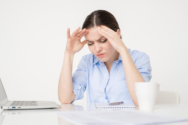 Gestreste of onrustige zakenvrouw raakt haar hoofd aan terwijl ze zich over het bureau buigt en probeert zich te concentreren