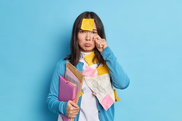 Gestreste, vermoeide student huilt van teleurstelling heeft een deadline voor de voorbereiding op het examen voelt zich verdrietig om een fout te maken in cursussen.