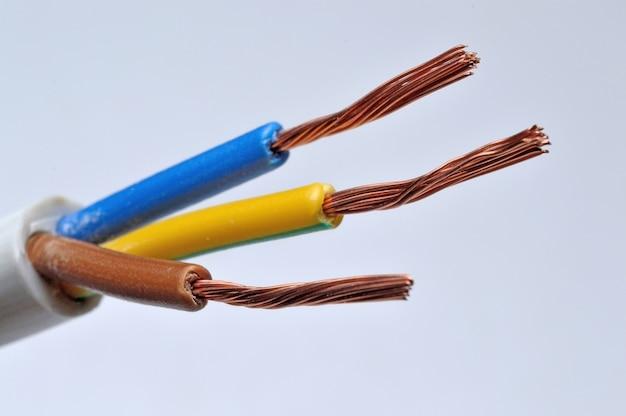 Gestripte driedraads elektrische kabel aan een lamp