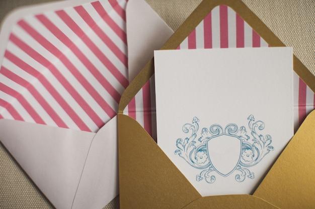 Gestripte enveloppen met witte kaarten binnen