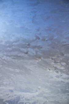 Gestructureerde vorstpatronen op het glas. ijskristallen op het raam op een koude, ijzige dag in de winter.