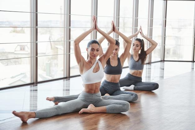 Gesynchroniseerde opgeheven armen omhoog. drie meisjes heeft fitness dag in de kamer met houten vloer en grote ramen