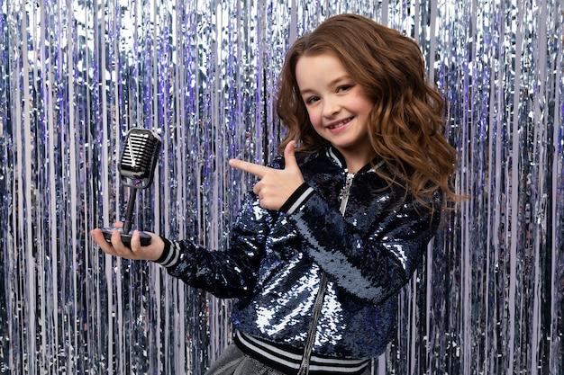 Getalenteerd stijlvol meisje met een retro microfoon in de hand op een glanzende vakantiemuur