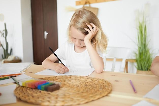 Getalenteerde blonde europese jongen die leuke tijd thuis heeft, aan tafel zit met het hoofd op zijn hand, in beslag genomen door tekenen, schetsen, met zwart potlood. geconcentreerde schooljongen die aan houten bureau kleurt