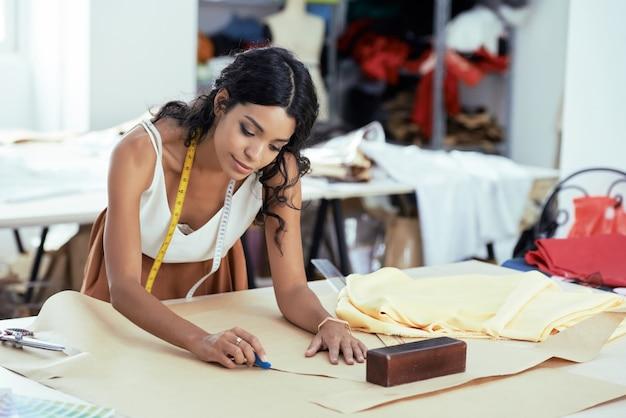 Getalenteerde creatieve jonge kledingontwerper werkt aan patroon voor nieuwe jurk