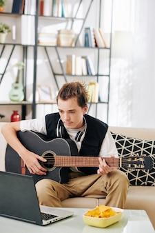 Getalenteerde creatieve tienerjongen die tutorial op laptop bekijkt bij het leren gitaar spelen of een nieuw liedje spelen