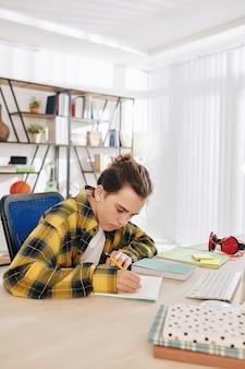 Getalenteerde creatieve tienerstudent die schetsen voor schoolproject tekent