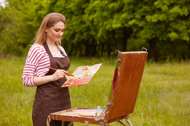 Getalenteerde geïnspireerde kunstenaar met professionele apparatuur in beide handen, schilderend in de open lucht, dol op de natuur, gestreept sweatshirt