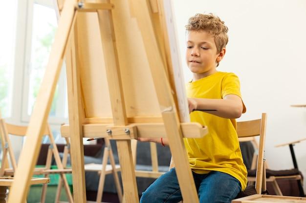 Getalenteerde jongen die zich goed voelt tijdens het schilderen op de kunstacademie