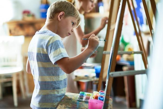 Getalenteerde kleine jongen schilderij foto