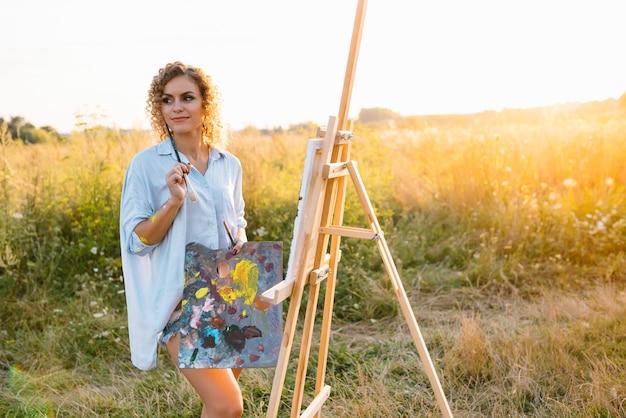 Getalenteerde kunstenaar in de buitenlucht mengt verf voor haar nieuwe project terwijl ze penselen vasthoudt.