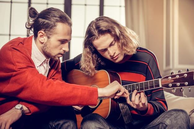 Getalenteerde leerling. professionele gitaarleraar met baard die het druk heeft met lesgeven aan zijn getalenteerde student